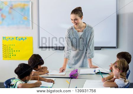 Happy female teacher teaching students in classroom