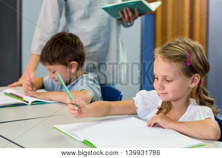 Smiling schoolchildren writing on book against teacher in background