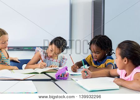 Schoolchildren writing on books in classroom