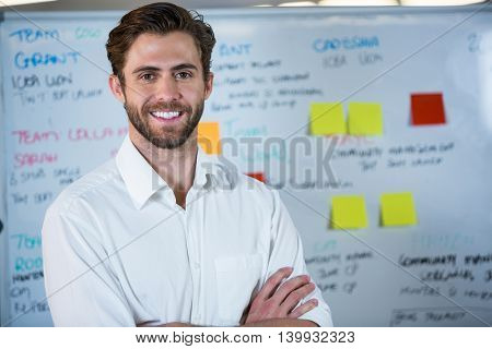 Portrait of smiling businessman with arms crossed against whiteboard in office