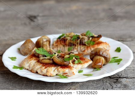 Roasted Turkey fillet with cheese and mushrooms on a plate and on old wooden background. Delicious Turkey cutlets recipe. Closeup