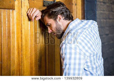 Depressed young man leaning on wooden door