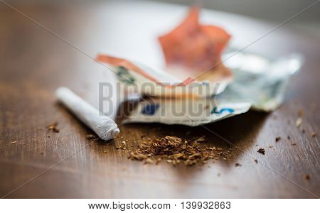 substance abuse, nicotine addiction, drug sale and smoking concept - close up of marijuana joint and money