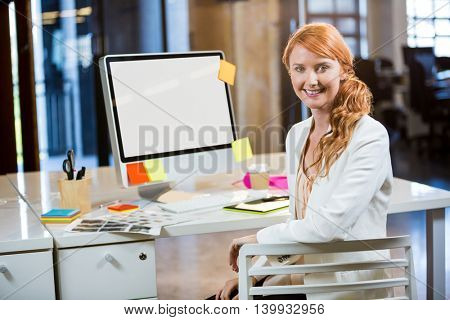 Portrait of businesswoman smiling while sitting by computer desk in creative office