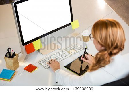 High angle view of creative businesswoman working at computer desk in office