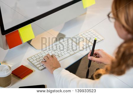 High angle view of businesswoman working with graphics tablet at desk in office