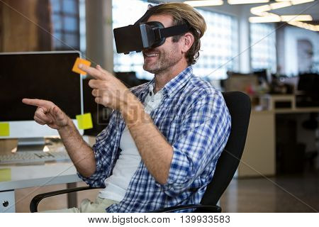 Creative businessman gesturing while using virtual reality simulator in office