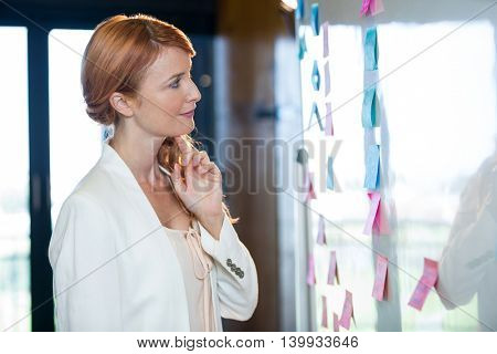 Side view of pretty businesswoman looking at sticky notes stuck to whiteboard in office