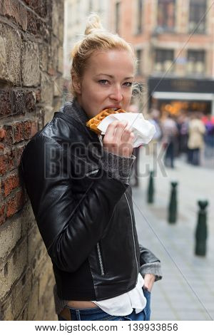 Urban portrait of young beautiful female tourist eating belgian waffle to go on street of Brussels, Belgium.