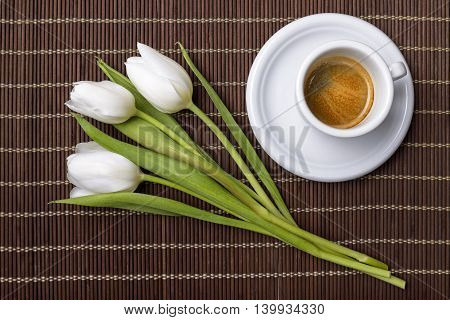 coffee and three white tulips on wooden placemat for spring breakfast