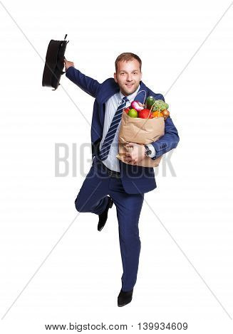 Happy young businessman run home with shopping bags full of groceries isolated at white background. Healthy food shopping. Paper package with vegetables and fruits