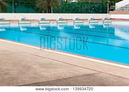 blue water in swimming pool reflects with sunlight, blue tile ceramic for swimming races and water sports.