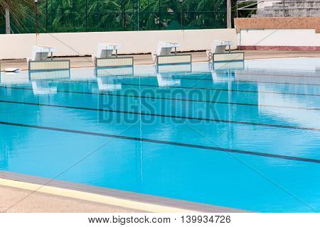 blue water wave in swimming pool reflects with sunlight blue tile ceramic to swimming race and water sports.
