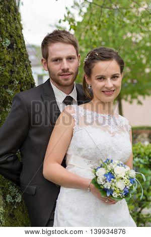 newlywed newlyweds in park near a tree