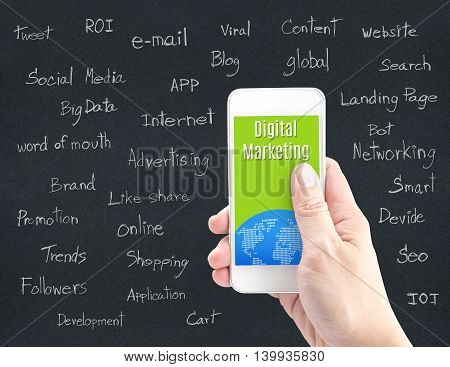 Hand holding smart phone with Digital Marketing word and word about digital marketing on black paper Digital Marketing concept.