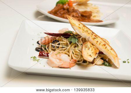 Stir-fried spicy spaghetti with shrimp and garlic bread