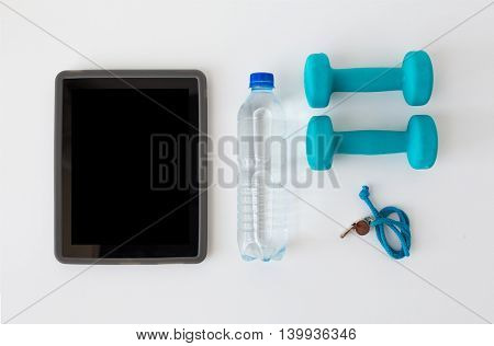 sport, healthy lifestyle and objects concept - tablet pc computer with dumbbells, whistle and water bottle over white background