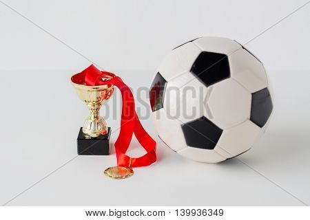 sport, achievement, championship, competition and success concept - close up of football or soccer ball with golden medal and cup over white background