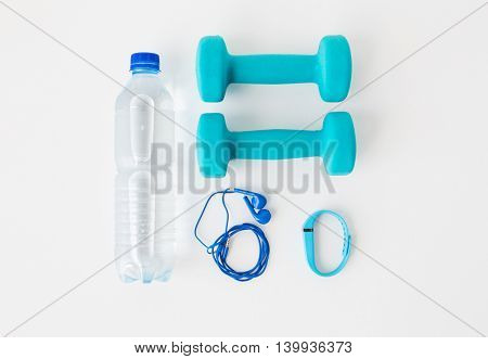 sport, healthy lifestyle and objects concept - close up of dumbbells, fitness tracker, earphones and water bottle over white background