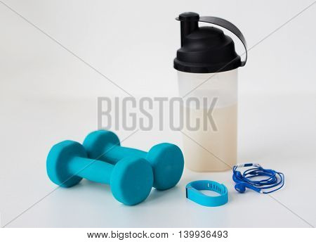 sport, healthy lifestyle and objects concept - close up of dumbbells, fitness tracker, earphones and protein shake bottle over white background