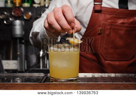 Barman is finishing up cocktail with lemon no face