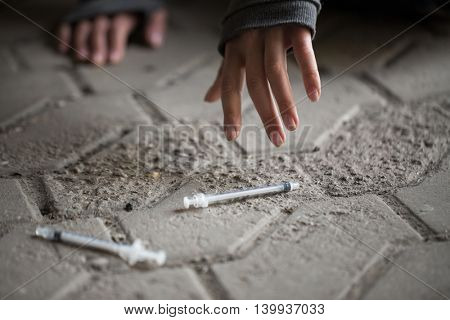 substance abuse, addiction, people and drug use concept - close up of addict woman hands and used syringes on ground