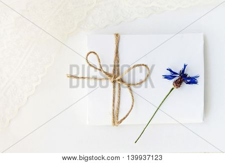 Delicate save-the-date card, background for writing. White empty envelope handcrafted, blurry lace, dried sweet blue flower.