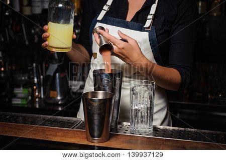 Barman is making cocktail at the bar