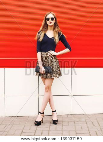 Fashion Beautiful Woman In Leopard Skirt Sunglasses Handbag Clutch Over Red Background