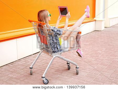 Beautiful Young Woman Sitting In Shopping Trolley Cart Over Colorful Orange Background