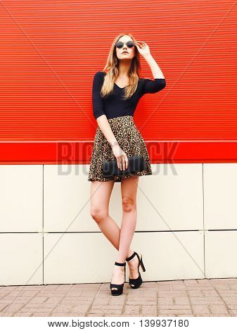 Fashion Beautiful Woman In Leopard Skirt Sunglasses Handbag Clutch Posing Over Red Background