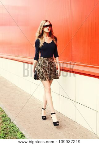 Fashion Beautiful Young Woman In Leopard Skirt And Sunglasses With Handbag Clutch Walking Outdoors