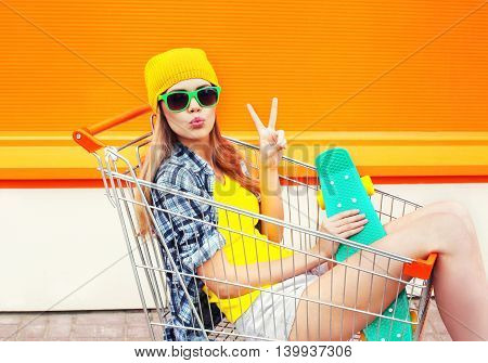 Fashion Pretty Cool Girl In Shopping Trolley Cart With Skateboard Over Colorful Orange Background