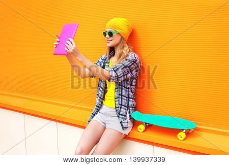 Fashion Pretty Cool Girl Makes Self Portrait On Tablet Pc Over Orange Colorful Background