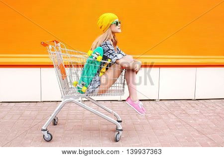 Fashion Pretty Cool Girl Sitting In Trolley Cart Over Colorful Orange Background