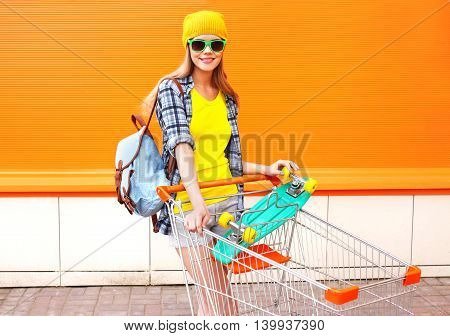 Fashion Pretty Cool Girl With Shopping Trolley Cart And Skateboard Over Colorful Background