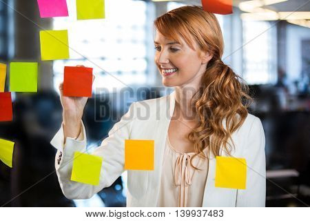 Smiling businesswoman writing on adhesive notes stuck to glass in creative office