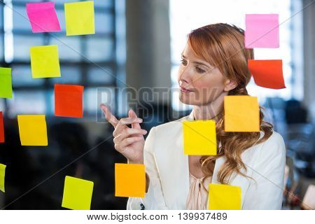 Businesswoman pointing at sticky notes stuck on glass in creative office