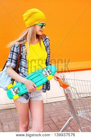 Fashion Pretty Girl With Shopping Trolley Cart Skateboard Over Colorful Orange Background