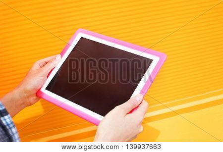 Female hands holding using digital tablet pc over colorful orange background