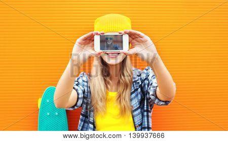 Pretty Blonde Woman Makes Self-portrait On Smartphone Over Colorful Orange Background