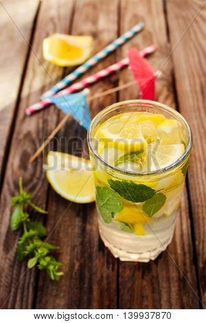 Drink with lemon, mint, ice, water on wooden background. Toned image