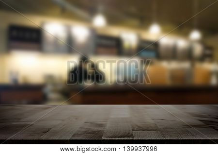 Selected focus empty brown wooden table and Coffee shop restaurant blur background with bokeh image. for your photomontage or product display