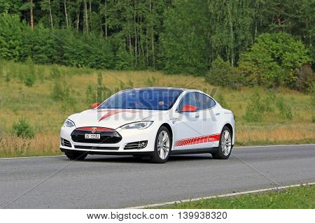 PAIMIO, FINLAND - JULY 24, 2016: Red and white Tesla Model S unique design Electric Vehicle moves along green rural road in South of Finland at summer.