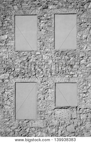 Irregular stone wall with four blind windows. Gray background. Copy space