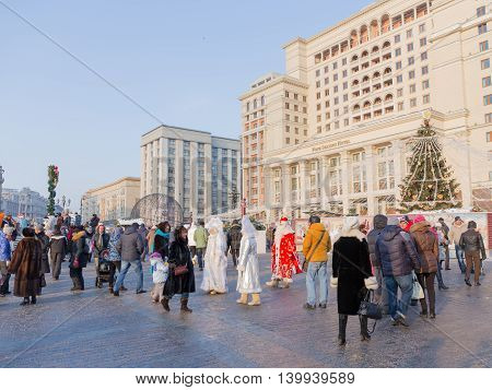 Moscow - January 7 2016: Happy people and tourists walk on Manezhnaya Square during the winter holidays and Christmas tree decorated with Christmas January 7 2016 Moscow Russia