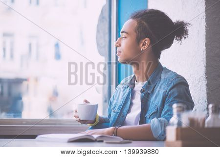 Dream big. Happy and thoughtful young man holding cup of coffee and being far away with his thoughts while sitting in a cafe