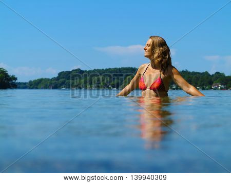 summer vacations image with adult milf woman relaxing in a beautifil lake