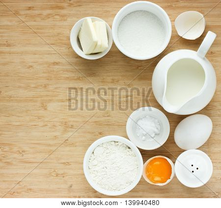 Ingredients for making pancake - flour eggs salt sugar butter milk. View from above. Rustic background with free text space. Ingredients for the dough. Food background