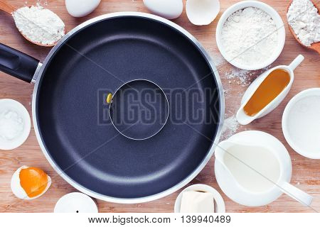 Cooking pancakes food background: ingredients and empty pan on a wooden background top view toning